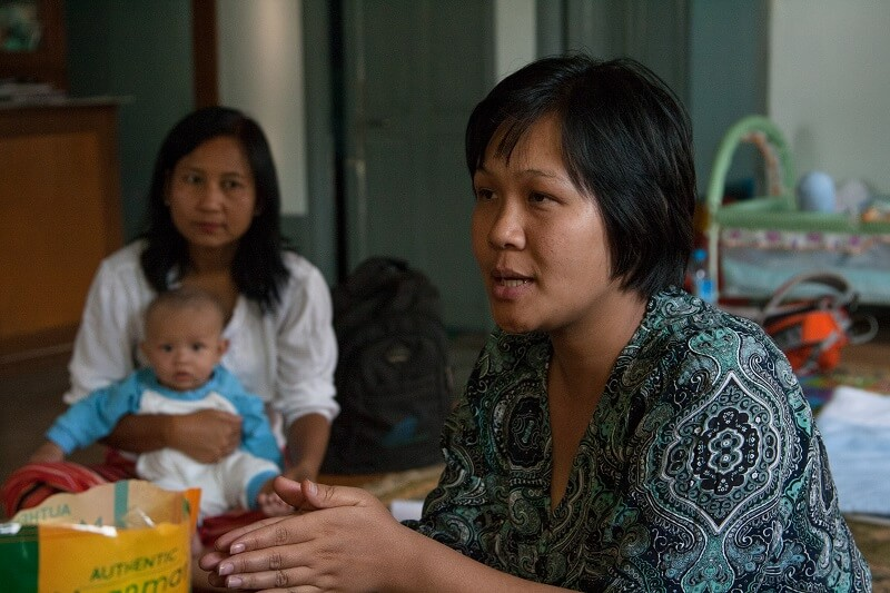 Shining carries on the discussion while one of the meeting's participants holds her son.
