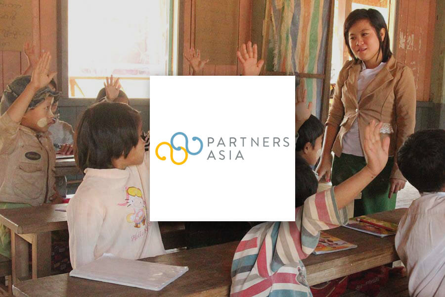 A teacher in class with young students. Partners Asia logo overlaid on top.